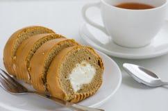 Rotolo del dolce di caffè con una tazza di tè Immagine Stock