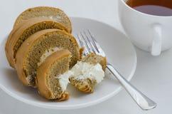 Rotolo del dolce di caffè con una tazza di tè Fotografie Stock
