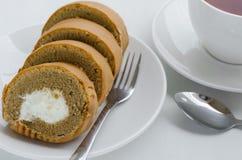 Rotolo del dolce di caffè con una tazza di tè Fotografia Stock