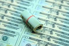 Rotolo del dollaro sulle banconote in dollari Immagine Stock