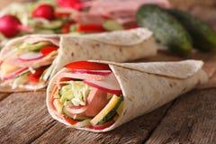 Rotolo del panino con il prosciutto e gli ortaggi freschi macro orizzontale immagini stock