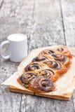 Rotolo del seme di papavero di recente al forno sulla tavola del Th con la tazza bianca del latte Fotografie Stock Libere da Diritti