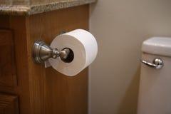 Rotolo del tessuto di toilette allegato ad una vanità da una toilette Immagine Stock