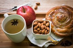 Rotolo della prima colazione, tè, mela, almods con backgroud di legno fotografia stock libera da diritti