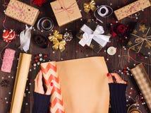 Rotolo di spiegamento della mano della donna di spostamento della carta kraft per il contenitore di regalo d'imballaggio di natal immagine stock
