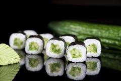 Rotolo di sushi con il cetriolo sopra fondo nero con la riflessione Immagini Stock