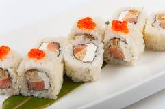 Rotolo di sushi con l'omelette ed il formaggio di Filadelfia con il caviale di color salmone e rosso immagine stock