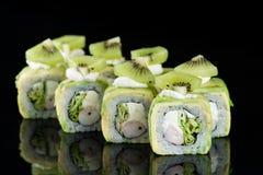 Rotolo di sushi con polpa di granchio, il kiwi e l'avocado sopra il backgrou nero fotografie stock