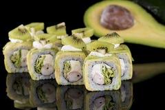 Rotolo di sushi con polpa di granchio, il kiwi e l'avocado sopra il backgrou nero Immagine Stock