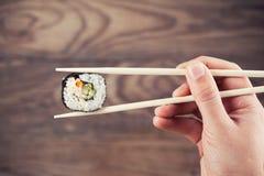 Rotolo di sushi della tenuta della mano facendo uso dei bastoncini Fotografia Stock