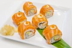 Rotolo di sushi di color salmone con formaggio cremoso sul piatto bianco, stile giapponese dell'alimento Immagini Stock