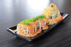 Rotolo di sushi di Maki fatto della cima di color salmone con l'alga del wakame - alimento giapponese Immagini Stock Libere da Diritti