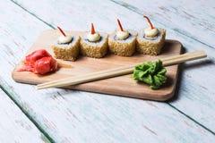 Rotolo di sushi su fondo di legno bianco Fotografia Stock