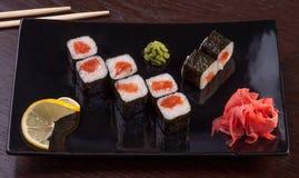 Rotolo di sushi su un piatto con lo zenzero ed il limone Fotografie Stock Libere da Diritti