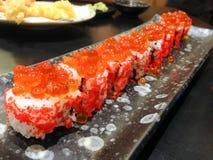 Rotolo giapponese del riso con le uova di color salmone sulla cima e sull'alga dentro, La immagini stock