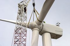 Large windmill being assembled by construction workers with a crane. Rotor of a large wind turbine is lifted into place by a crane during construction of a wind Royalty Free Stock Images