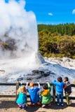 ROTORUA, NIEUW ZEELAND - OKTOBER 10, 2018: De kinderen letten op de uitbarsting van DameKnox geiser in wai-o-Tapu verticaal stock foto's
