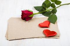 Rotrose, -herzen und -papier für Glückwünsche Lizenzfreies Stockfoto