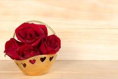 Rotrose im Goldkorb, Valentinsgruß-Tag, Hochzeitstag, hölzernes backg lizenzfreie abbildung