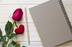 Rotrose mit Bleistift und leerem Notizbuch auf hölzernem Hintergrund Lizenzfreie Stockfotografie