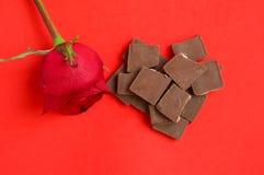 Rotrose mit Schokolade auf rotem Hintergrund Lizenzfreie Stockbilder