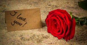 Rotrose und -anmerkung ich liebe dich über das Kraftpapier Stockfotos
