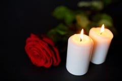Rotrose und brennende Kerzen über schwarzem Hintergrund Stockfotos