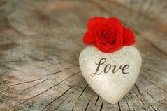 Rotrose und -herz auf hölzernem Hintergrund Liebes- und Valentinsgrußtageskonzept Stockfoto