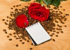 Rotrose und -notizbuch auf Kaffeesamen und hölzernem Hintergrund Stockbild