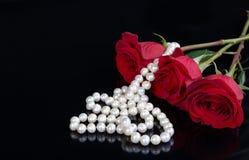 Rotrose und -perlen auf schwarzem Hintergrund Stockfotografie