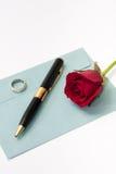 Rotrose und schwarzer Bleistift mit Verlobungsring auf dem blauen envel Stockbild