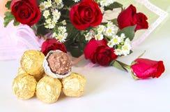 Rotrosen-Blumenblumenstrauß mit Schokoladenball Stockfoto