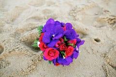 Rotrosenblume und purpurroter Orchideenhochzeitsblumenstrauß auf Sand Stockfoto
