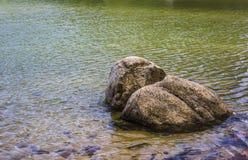 Rots in het meer Stock Foto
