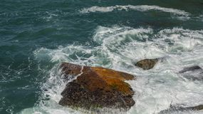 Rots in het overzees De golven die op een steenachtig strand breken stock foto's