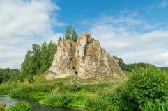 Rots met hout op de bank van een stroom, in de zomer Stock Afbeelding
