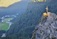 Rots met verlicht kruis boven een vallei Stock Afbeelding