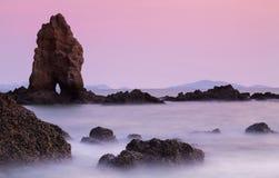 Rots op het strand met schemeringhemel Royalty-vrije Stock Afbeelding
