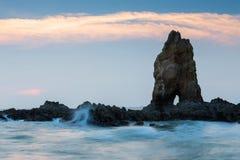 Rots over zeekust tijdens zonsondergang, natuurlijk landschap stock fotografie