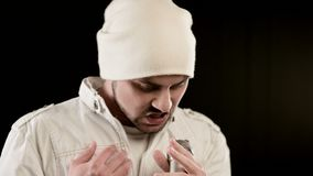 Rots van de close-up de frontman vocalist pop met een modieuze baard in witte kleren en een hoed met een microfoon in zijn handen stock video