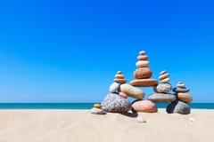 Rots zen piramide van kleurrijke kiezelstenen op een zandig strand op de achtergrond van het overzees Concept saldo, harmonie en  royalty-vrije stock foto