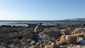 Rotsachtig die strand met plastic afval en afval wordt gevuld Schip en bergen op de achtergrond Langzame Motie stock videobeelden