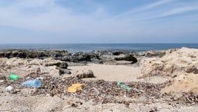 Rotsachtig die strand met plastiek en huisvuil wordt verontreinigd Afval en kringloopconcept stock videobeelden