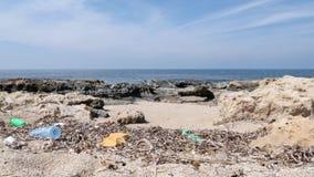 Rotsachtig die strand met plastiek en huisvuil wordt verontreinigd Afval en kringloopconcept Langzame Motie stock footage