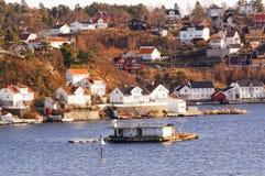 Rotsachtig eiland met gebouwen in fjorden, Noorwegen Royalty-vrije Stock Foto's