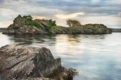 Rotsachtig eiland op de rivier in zonsondergangtijd Stock Afbeelding