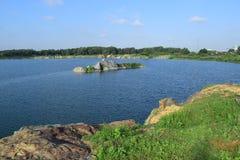 Rotsachtig meer met klein riviereilandje Stock Afbeelding