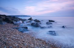Rotsachtig strand bij schemer Stock Afbeelding