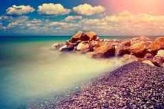 Rotsachtig strand bij zonsondergang Stock Afbeeldingen
