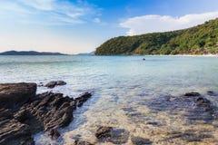 Rotsachtig strand en de oceaan met bergachtergrond Royalty-vrije Stock Foto's
